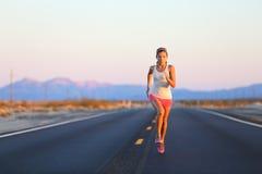 Rinnande kvinna som sprintar på väghuvudvägen Fotografering för Bildbyråer