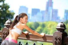 Rinnande kvinna som sträcker, når att ha joggat i New York fotografering för bildbyråer