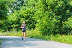 Rinnande kvinnalöpare som joggar på skogsportbanan royaltyfria bilder