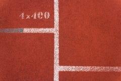 Rinnande löparbana och vit linje med nummer Arkivfoto