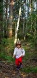 Rinnande liten flicka i skogen Arkivbild