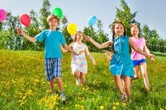 Rinnande lyckliga ungar med ballonger i grönt fält Royaltyfria Bilder