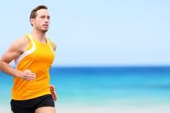 Rinnande man för stilig passform som joggar på kust på stranden royaltyfri foto