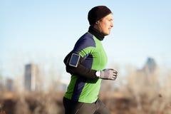 Rinnande man som joggar i höst till musik på telefonen Arkivfoto
