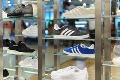 Rinnande och tillfälliga skor som är till salu i modeskolager Arkivfoto
