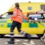 Rinnande oskarp paramedicinsk kvinna som drar gurneyen Royaltyfri Fotografi