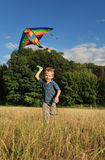 Rinnande pojke med flygdraken Royaltyfria Foton