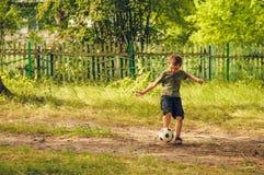 Rinnande pojke som spelar med bollen royaltyfri fotografi