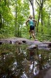 Rinnande skogslinga för ung kvinna förbi en ström med reflexion i vatten Fotografering för Bildbyråer