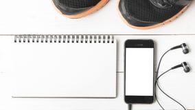 Rinnande skor, anteckningsbok och telefon Arkivbilder