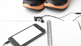 Rinnande skor, anteckningsbok och telefon Arkivfoto