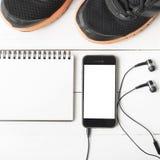 Rinnande skor, anteckningsbok och telefon Royaltyfri Fotografi