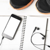 Rinnande skor, anteckningsbok och telefon Arkivfoton