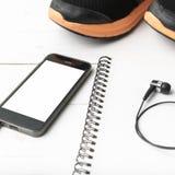 Rinnande skor, anteckningsbok och telefon Arkivbild