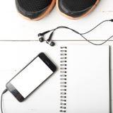Rinnande skor, anteckningsbok och telefon Royaltyfri Foto