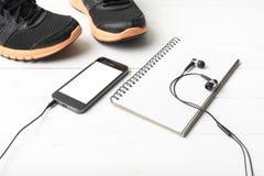 Rinnande skor, anteckningsbok och telefon Royaltyfria Bilder