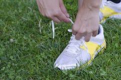 Rinnande skor - closeupen av kvinnan som binder skon, snör åt royaltyfri bild