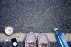 Rinnande skor för kvinnor och löpareutrustning på asfalt Utbildning på hårda yttersidor Löpareutrustningstoppur och musikspelare Arkivbilder