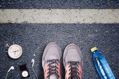 Rinnande skor för kvinnor och löpareutrustning på asfalt Utbildning på hårda yttersidor Löpareutrustningstoppur och musikspelare Royaltyfri Foto