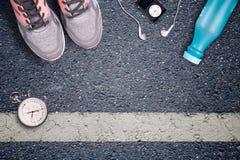 Rinnande skor för kvinnor och löpareutrustning på asfalt Utbildning på hårda yttersidor Löpareutrustningstoppur och musikspelare Royaltyfria Foton