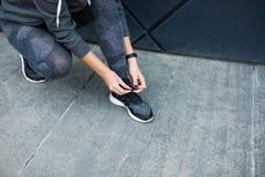 Rinnande skor - kvinnan som binder skon, snör åt Closeup av den kvinnliga sportkonditionlöparen som får klar för att jogga utomhu royaltyfri foto