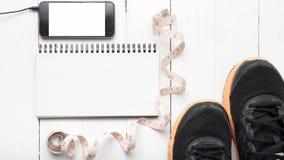 Rinnande skor som mäter bandet, anteckningsboken och telefonen Arkivbild