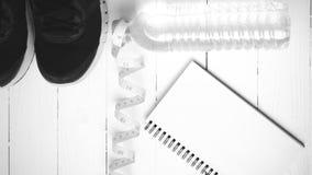 Rinnande skor som mäter bandet, dricksvatten och anteckningsboken, svärtar a Fotografering för Bildbyråer