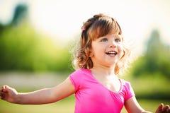 Rinnande stående för liten lockig lycklig flicka Arkivfoto