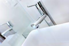 Rinnande vatten av en modern vattenkran i toaletten med lavoar Arkivfoton