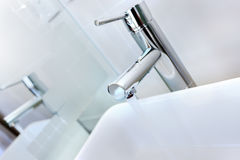 Rinnande vatten av en modern vattenkran i toaletten med lavoar Arkivbild