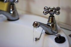 Rinnande vatten från en vattenkran i badrum arkivbilder