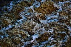 Rinnande vatten med blåa ljusa strimmor Royaltyfri Foto