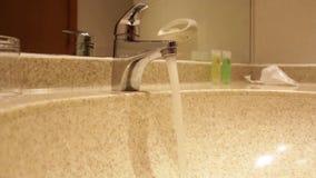 Rinnande vatten och kvinnan för vattenkran för hotellbadrumvask räcker att stänga det arkivfilmer
