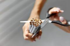 Rinunci l'immagine contro il fumo resa Smoking Il primo piano della donna passa le sigarette di taglio Fotografie Stock