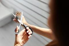 Rinunci l'immagine contro il fumo resa Smoking Il primo piano della donna passa le sigarette di taglio Fotografia Stock