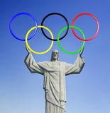 Rio 2016. Christ The Redeemer, On Top Of Corcovado Mountain In Rio De Janeiro. Holding Olympic Rings. Stock Photos