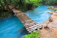 Rio celeste and small wooden bridge. Tenorio national park Costa Rica Royalty Free Stock Photography