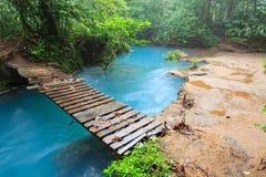 Rio celeste and small wooden bridge. Tenorio national park Costa Rica Royalty Free Stock Photo