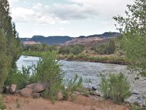 Rio Chama near Abiquiu, New Mexico. Early evening as the Rio Chama flows among the colorful cliffs near Abiquiu, New Mexico stock photography