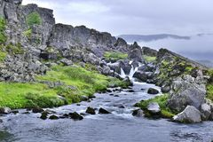 Rio com a cachoeira pequena no parque nacional de Thingvellir na luz de nivelamento foto de stock
