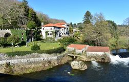 Rio com moinho de água e casa tradicional do pazo com jardins, árvores e o céu azul Ponte Maceira, Coruna, Espanha fotos de stock