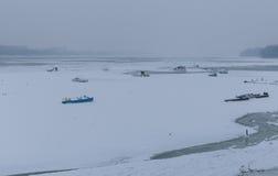 Rio congelado Danúbio no gelo, barcos de pesca Fotografia de Stock Royalty Free
