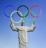 Rio 2016 Cristo il redentore, sopra la montagna di Corcovado in Rio de Janeiro Tenuta degli anelli olimpici Fotografie Stock