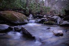 Rio da água fresca com fotografia lenta da velocidade do obturador e rochas com musgo fotografia de stock