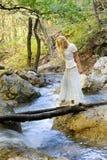 Rio da floresta do cruzamento da menina pela ponte de madeira Imagem de Stock Royalty Free