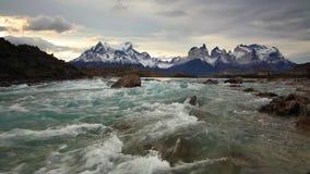 Rio da montanha no por do sol com uma vista das montanhas Torres del Paine, o Chile