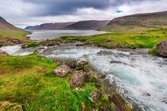 Rio da montanha que flui no lago entre as montanhas, Islândia Fotos de Stock Royalty Free