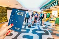 Rio de Janeiro, Brésil - 27 août 2017 : Illustration éditoriale de main tenant un passeport brésilien avec une note de 5 reais à  Photographie stock libre de droits