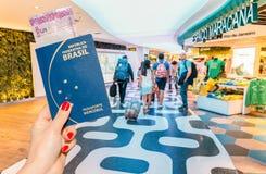 Rio de Janeiro Brasilien - 27 Augusti, 2017: Redaktörs- illustration av handen som rymmer ett brasilianskt pass med en 5 reais an Royaltyfri Bild
