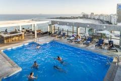 Rooftop view of swimmers at a luxurious hotel penthouse pool and bar overlooking Copacabana Beach in Rio de Janeiro, Brazil. Rio de Janeiro, Brazil - Dec 17 royalty free stock photos